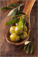 Muursticker  Spoon with green olives on a wooden table - Elena Schweitzer