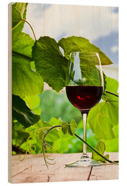 Hout print  glass with red wine in vineyard